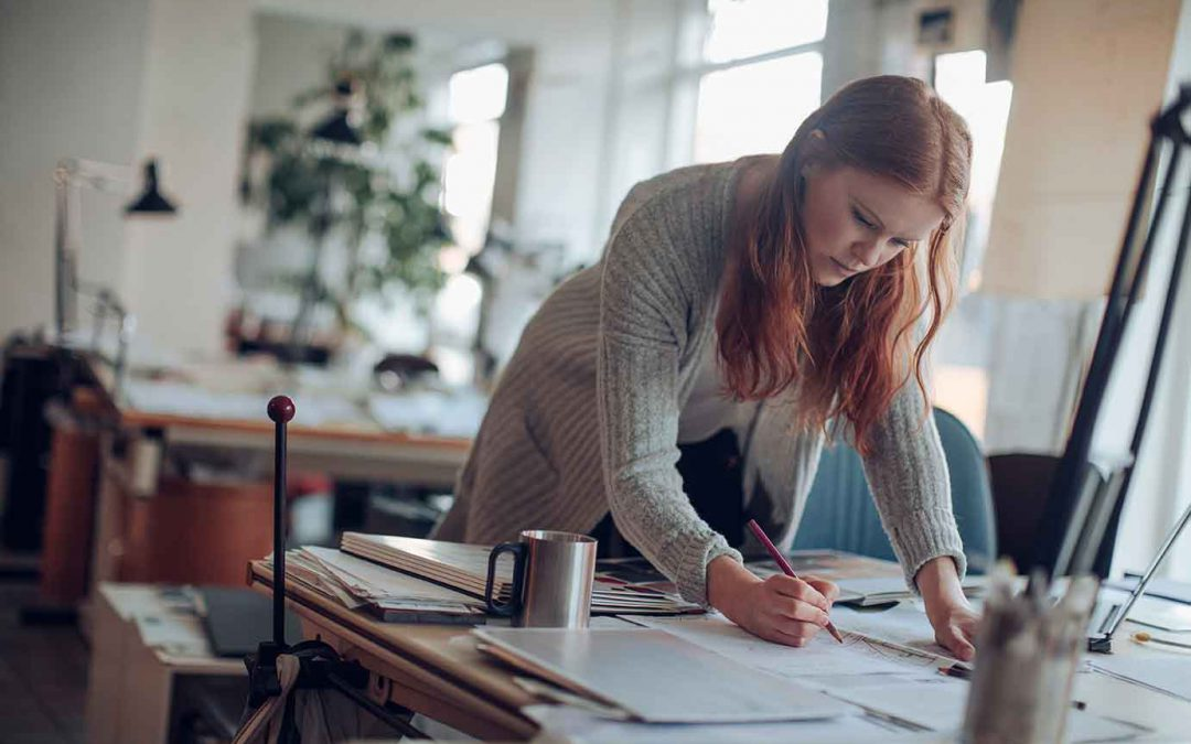 red-headed woman works intently at her home office